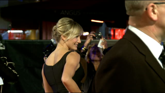 Gambit' London premiere Colin Firth along and greeting crowd and signing autographs / Cameron Diaz posing for photographers / back view Diaz and...