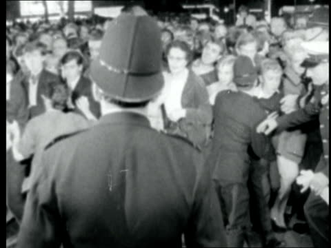 'goldfinger' premiere england london leicester square sign 'goldfinger' tilt to crowds outside bv of people going in ms police push crowd back ms... - film premiere stock videos and b-roll footage