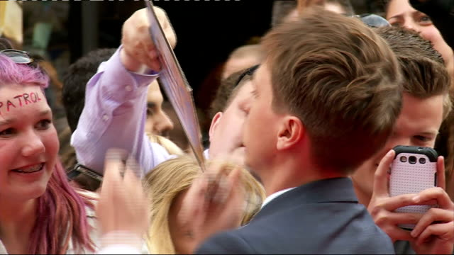 inbetweeners 2 premiere: arrivals and interviews; joe thomas signing autograpsh and posing for selfies with fans / emily berrington on red carpet /... - emily berrington stock videos & royalty-free footage