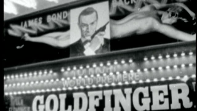 james bond 50th anniversary celebrated; lib / tx 17.9.1964 england: london: ext b/w 'goldfinger' sign on cinema crowd of people outside for film... - 作品名 ジェームズ・ボンド点の映像素材/bロール