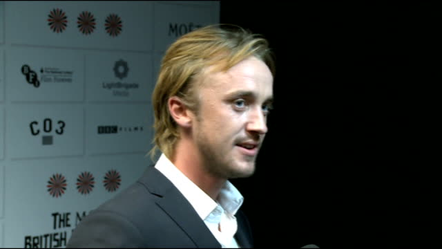 stockvideo's en b-roll-footage met moet british independent film awards 2012 interviews tom felton along then posing with bottle of champagne / felton chatting to press tom felton... - terry gilliam