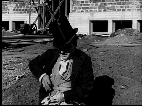 1924 B&W Film montage MS aristocratic man lying in dirt with legs up/ sitting up and pulling pocketwatch from pocket and checking to see if it's ticking/ man looking relieved/ WS man getting up and walking off