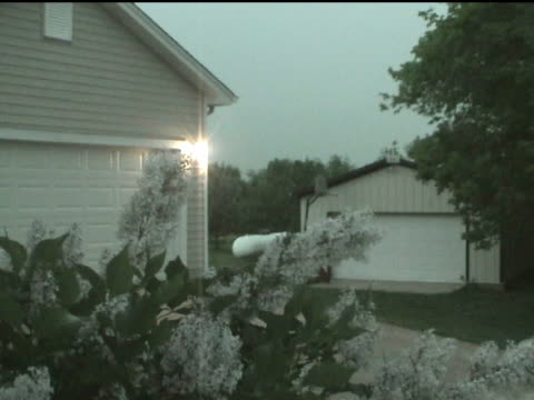 film montage ms bushes and suburban garage at dusk as storm approaches/ lightning striking in distance/ lightning striking tree as camera turns sideways/ usa - slug stock videos & royalty-free footage