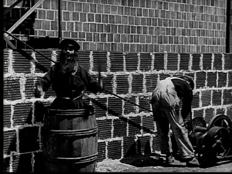1924 B&W Film montage MS construction worker standing near wall as crazy man pops up from barrel and cuts rope/ MS large stone with Roman numerals falling and splashing wet cement