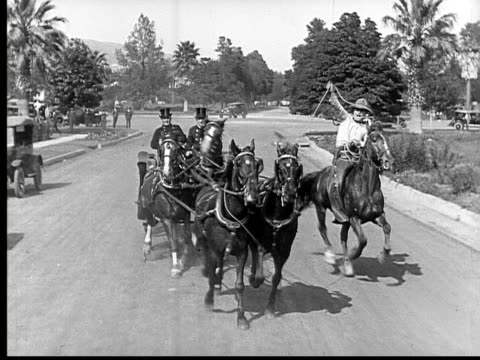 1924 B&W Film montage WS cowboy lassoing runaway horsedrawn carriage/ MS cowboy pulling lasso/ MS horses moving off road/ MS cowboy pulling lasso/ WS cowboy catching up to horses