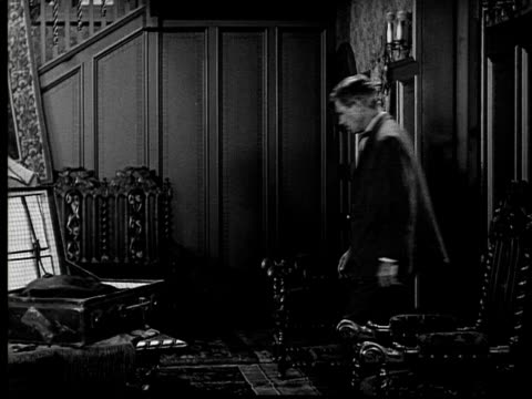 1924 B&W Film montage MS man entering room as woman bosses him/ MS woman pointing to open suitcase as man walks over and grabs contents