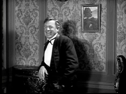 1924 b&w film montage ms man in tuxedo laughing/ woman talking and looking wistful with stern butler in background  - tail stock videos & royalty-free footage