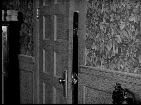 vidéos et rushes de 1924 b&w film montage ms man opening door and looking in/ comfortable old pants sitting on chair  - 1924