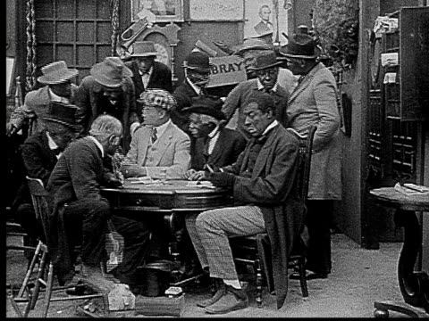 1916 b&w film montage ms man putting card between toes to pass under table during poker game/ man taking card and looking around  - poker card game stock videos & royalty-free footage