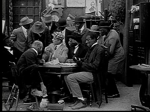 1916 b&w film montage ms man putting card between toes to pass under table during poker game/ man taking card and looking around  - solo uomini video stock e b–roll