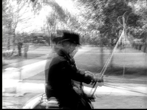 1924 b&w film montage ms men riding on very fast horsedrawn carriage/ ws fast carriage passing stopped horse and carriage on side of road  - 1924年点の映像素材/bロール