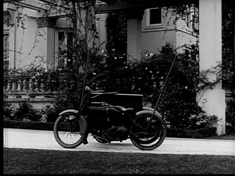 1924 b&w film montage ws motorcycle appearing to have no driver stopping in front of fancy home/ man popping out of box attached to cycle with bow and arrow and looking around  - 1924 stock videos and b-roll footage
