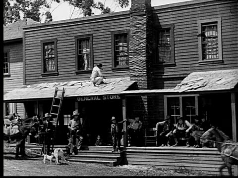 vídeos de stock, filmes e b-roll de 1924 b&w film montage/ ws old west-style scene with cowboys in front of general store/  ms horsedrawn carriage pulling up/ men on porch helping men out of carriage/ will rogers in top hat greeting cowboys on porch  - prefeitura