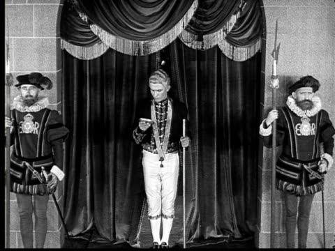 1924 B&W Film montage MS page entering king's court and announcing guest/ title card with dialogue/ MS smiling king sitting on throne