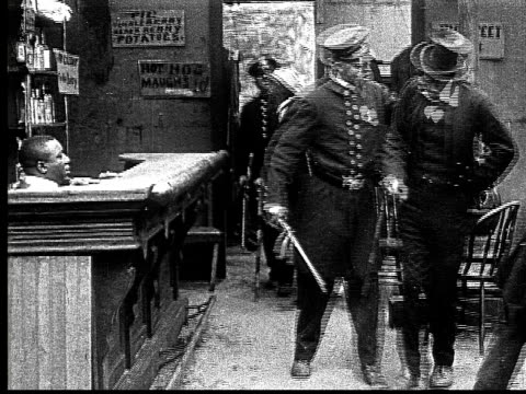 1916 b&w film montage ms police escorting arrested men out of bar/ men getting into police wagon  - aggression stock videos & royalty-free footage