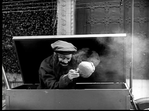 1924 B&W Film montage MS sinister bearded man popping out of box, lighting bomb, and throwing it/ bomb exploding in front of building/ horsedrawn carriage driving off