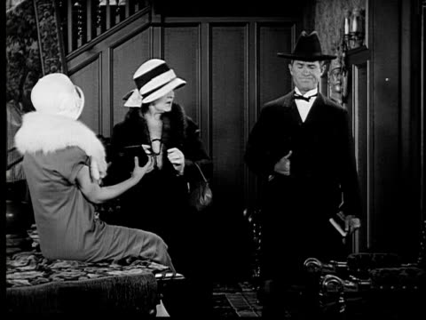 stockvideo's en b-roll-footage met 1924 b&w film montage ms two women putting on makeup and preparing to go out when man enters in tuxedo and cowboy hat/ woman scolding him and making him put on top hat  - cowboyhoed