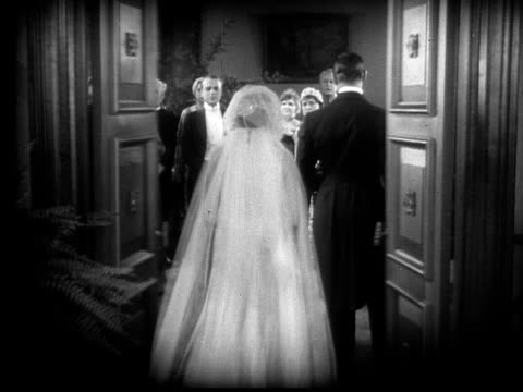 1928 B/W Film montage wide shot bride talking to two men and walking out of room/ walking through doors/ medium shot angry bride yelling at groom and tearing paper up