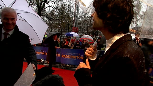 'paddington' premiere: red carpet arrivals; england: london: leicester square: ext / raining red carpet / fans with umbrellas / ben whishaw interview... - ben whishaw stock videos & royalty-free footage
