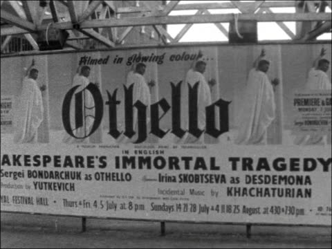 Premiere of Russian film of 'Othello' ENGLAND London EXT Royal Festival Hall Film posters Actresses selling programmes Unidentified man and woman...