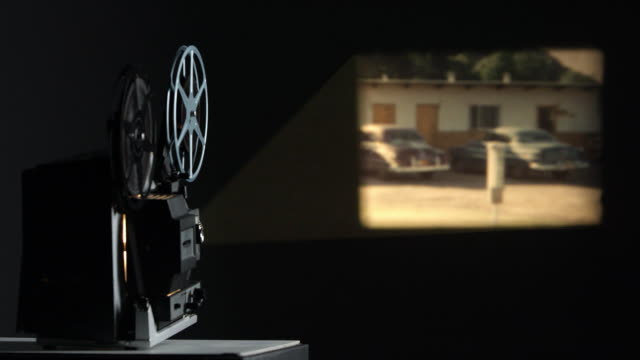 film projected onto wall playing old film - 映画館点の映像素材/bロール