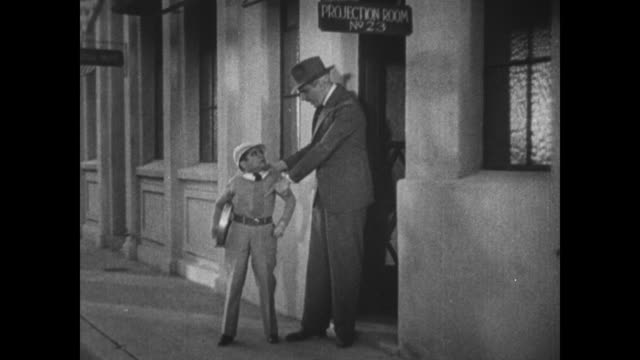 1931 film projectionist (george hayes) gives movie 'stolen jools' to boy (billy rhodes) who is accosted outside by police detective (eddie kane) - 1931 stock videos & royalty-free footage