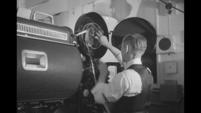 film projector / men with film reel / man loading and threading projector / projection booth behind viewing room with people talking and reading /... - proiettore cinematografico video stock e b–roll