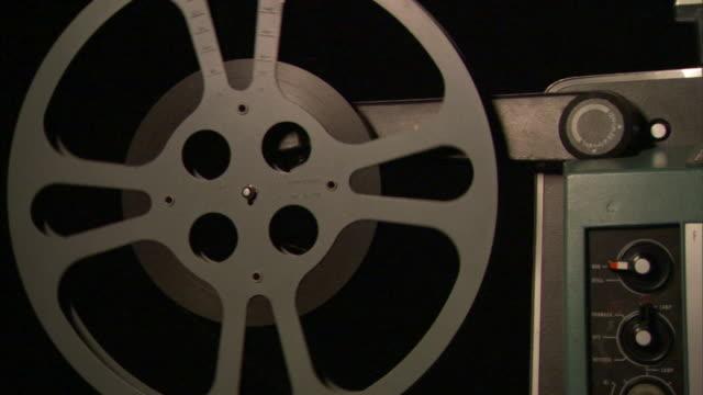 vídeos y material grabado en eventos de stock de cu film reel spinning as film is projected/ los angeles, california - equipo de proyección
