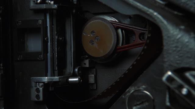 vídeos de stock, filmes e b-roll de a film reel winds inside a camera. available in hd. - câmera de filmar