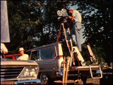 film set for a 1964 studebaker commercial; film camera is on tripod in the back of a studebaker wagonaire / angle on film camera and cameraman in the... - film set stock videos & royalty-free footage