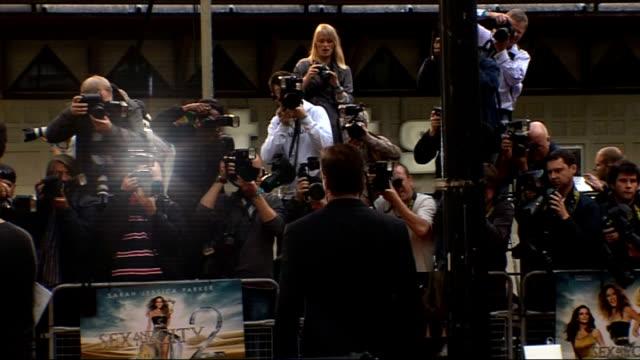 vídeos y material grabado en eventos de stock de 'sex and the city 2' london premiere: celebrity arrivals and interviews; cynthia nixon arriving, back view posing for photographers chris noth... - autografiar