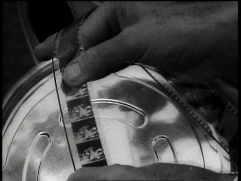 vídeos y material grabado en eventos de stock de film strip held and scrolled over film can / hollywood, california, united states - view from below