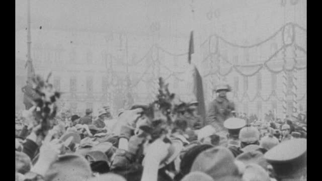 [film taken by noted world traveler lowell thomas] a vast crowd with men holding onto elevated poles decorated with garlands and a military parade... - ホームカミング点の映像素材/bロール