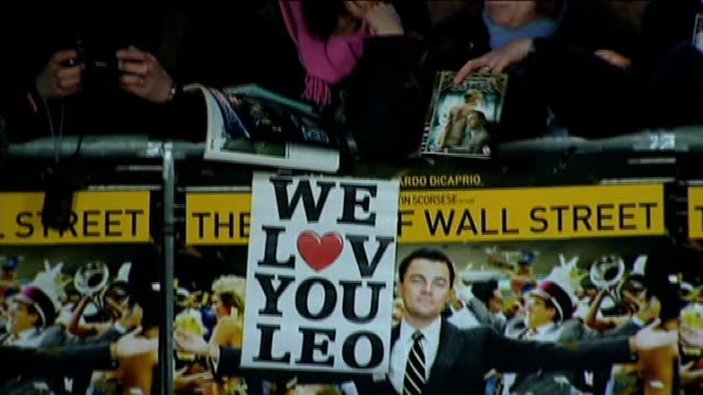 'The Wolf of Wall Street' premiere Robbie posing / fan banner reading 'We Love You Leo' TILT UP fans behind barriers / DiCaprio speaking to press