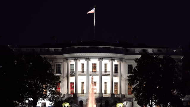 film tilt down night architecture of white house a washington dc con bandiera degli stati uniti, district of columbia usa - la casa bianca washington dc video stock e b–roll