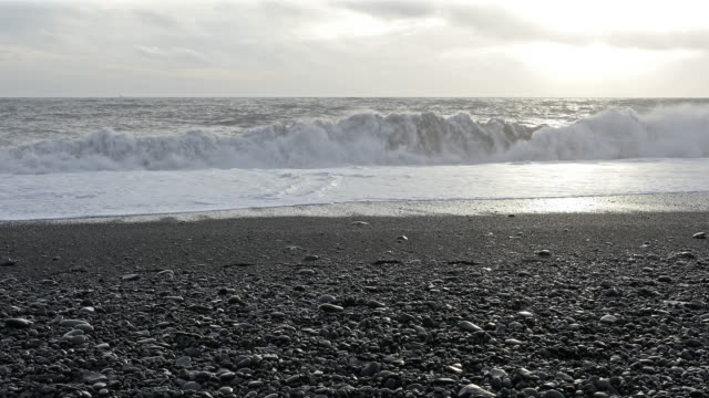 film tilt shot huge wave at black beach vik iceland - dyrholaey stock videos & royalty-free footage