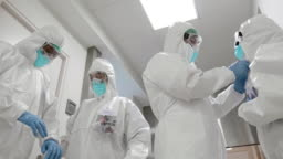 Film tilt slow motion video of medical team helping each other with protective equipment at hospital corridor