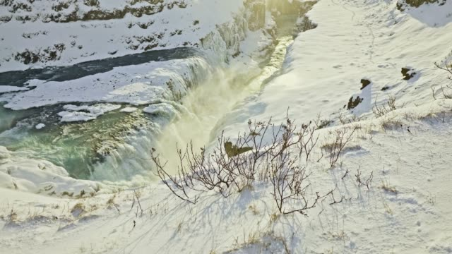 Film tilt video of people visiting Gulfoss waterfall at sunset