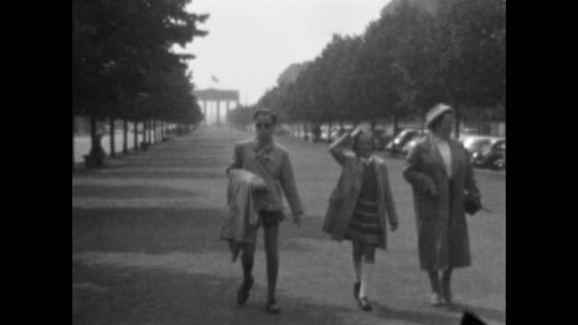 filmed between 1951 and 1954 tourists walk along the street of the 17th june with the brandeburg gate behind them street sign mittelstraße... - 1950 stock-videos und b-roll-filmmaterial