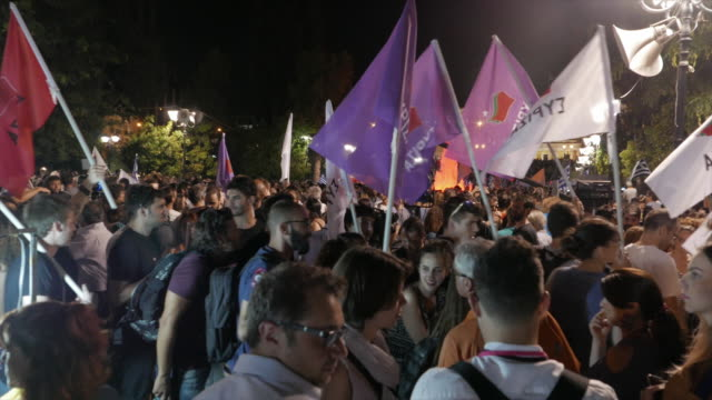 filmed moments after referendum results over bailout terms were announced front view of greek parliament people wave white red and purple flags night... - ユーロ圏債務危機点の映像素材/bロール