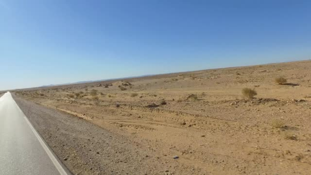 filming from the car like a drone. driving on a road in the desert - pjphoto69 stock videos & royalty-free footage