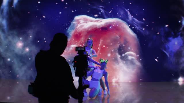 vidéos et rushes de tournage de la danse spatiale. danseurs synchronisés exécutant sur le fond de projection. projection avec univers et nébuleuses. silhouette de cameraman - caméraman