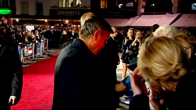 vídeos de stock, filmes e b-roll de 'the ides of march' london premiere; england: london: leicester square: ext / night george clooney signing autographs on red carpet - autografando