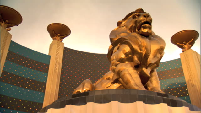 tu ws mgm logo mascot gold statue leo the lion at entrance of mgm grand las vegas hotel casino blue gray sky above - mgm grand las vegas stock videos & royalty-free footage