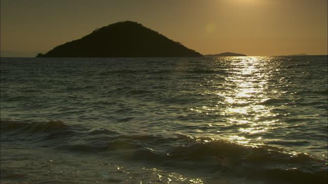 vídeos de stock e filmes b-roll de filtered shot of waves gently lapping on the shoreline of lake malawi. - malávi