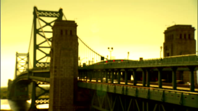 vídeos de stock e filmes b-roll de filtered soft angled ws suspension bridge w/ philadelphia anchorage fg pan traffic lanes new jersey alternate ben was delaware river bridge - ponte ben franklin