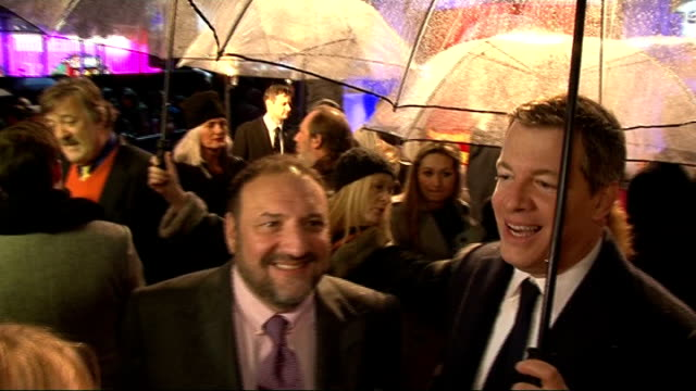'Sherlock Holmes A Game Of Shadows' red carpet interviews Stephen Fry speaking with reporter underneath umbrella / Side view Robert Downey Jr...