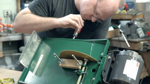 vídeos de stock e filmes b-roll de final assembly of trim saw machine tool as workman tightens screws of welded steel chassis / redlands, california, usa - confiabilidade