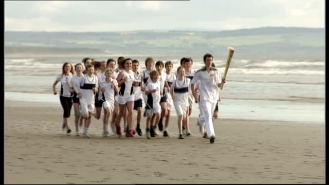 final day of torch relay lib scotland fife ext group of children running along beach with london 2012 olympic torch as recreate famous scene from... - olympic torch stock videos & royalty-free footage