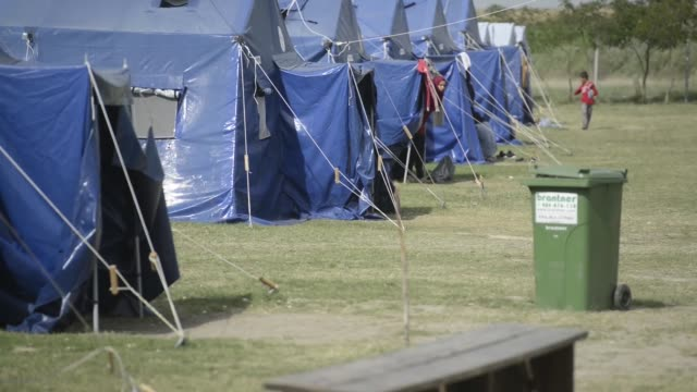 A final few refugees stand near tents in an almost deserted camp in Kanjiza Serbia on Thursday September 17 2015